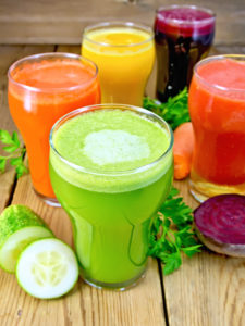 Five tall glasses with the juice of carrot, cucumber, beetroot, tomato and pumpkin with vegetables and parsley on a wooden boards background